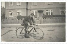 A man riding a Antique / Vintage BICYCLE