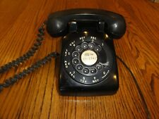 Old rotary dial desk phone in black.
