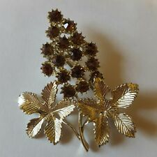 A beautiful gold tone flower themed brooch with amber coloured stones.