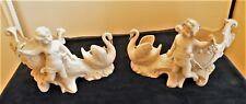 Paire de statuettes en biscuit, angelots, cornes d'abondance et cygnes