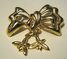 Gorgeous gold tone metal brooch in a bow design with bow charms