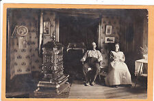 Real Photo Postcard RPPC - Man and Woman in a Parlor with Great Stove