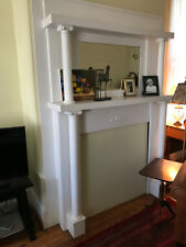Elegant antique fireplace mantel with beveled glass mirror, decorated columns