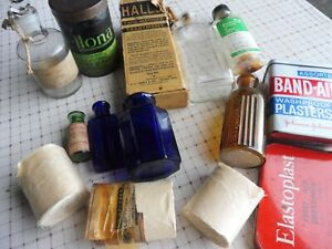Various vintage first aid items including CELLONA bandage tin and various bottle
