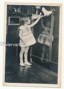 Vintage photo - little girl feeding porcelain dog statue on antique furniture