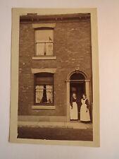 2 Frauen mit Schürze stehen im Hauseingang - Dienstmädchen ? / Foto England