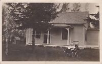 BABY IN CARRIAGE IN FRONT OF HOUSE/DOG HOUSE - Real Photo AZO Postcard * RPPC