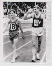 Australia's Ron Clarke salutes the crowd as he walks around 7/10/65 -Press Photo
