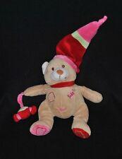 Peluche doudou ours brun beige BABY NAT' tenant 1 bonbon bonnet rouge 22 cm TTBE