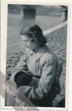 Woman in coat sitting by a river - vintage photo