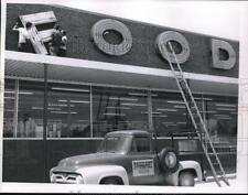 1959 Press Photo Three men fixing up signage of a food store