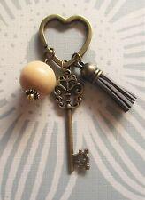 Llavero corazón en bronce con llave, bola de madera natural y borla de ante gris