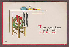 A Real Jolly Christmas c1915 Postcard Stockings Hanging on Mantle Wreath & Chair