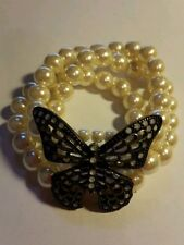 A lovely elasticated bracelet with white beads and metal butterfly