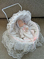 "Vintage bisque and cloth baby doll in metal carriage 7"" high"