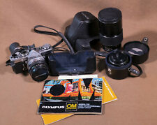 Olympus Om-1 film camera body with three lenses