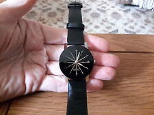Brand new silver watch with a 3cm black face gold hands and pyramid glass