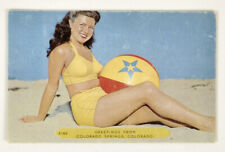 Vintage postcard girl in a swimsuit pin-up on the beach 1950s