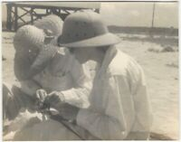 Woman & Man in Sun Hats Examine Fishing Rod on Beach at Seaside Vintage Snapshot