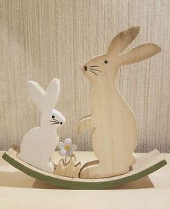 Hasenpaar auf Wippe aus Holz mit einer kleinen Blume