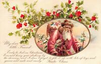Christmas Postcard Pink Suited Santa Claus Basket of Toys Tree Snow Holly~125519