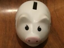 A medium ceramic piggy bank with an angry face and floral decoration