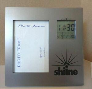HOWARD MILLER   ALARM DATE TIME CLOCK ON PICTURE FRAME