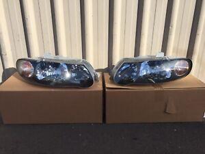 HOLDEN VX VU COMMODORE S SS BLACK HEADLIGHTS LAMPS NEW PAIR GENUINE GM STORM