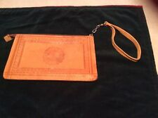 Tan leather embossed wristlet clutch with handle attached to the zipper.