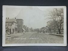 1916 real photo postcard ...LANSING IOWA....DOWNTOWN STREET SCENE..unpaved/quiet