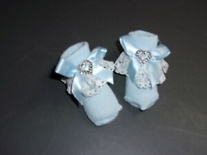 Newborn socks with satin bows, and a silver Heart decoration New