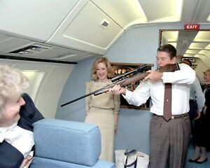 PRESIDENT RONALD REAGAN AIMING A RIFLE ABOARD AIR FORCE ONE - 8X10 PHOTO (RT784)