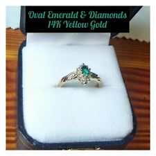 VINTAGE OVAL EMERALD FLANKED BY SPARKLING DIAMONDS SET IN A 14K YELLOW GOLD RING