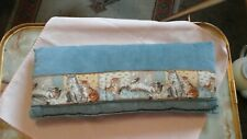 SMALL LONG BLUE VELVET STYLE MATERIAL CUSHION WITH A KITTEN PATTERN.