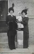 TWO PRETTY WOMEN IN BLACK AND AN ADORABLE BABY POSE IN CITY SETTING-VINTAGE RPPC