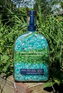 Woodford Reserve 750mL bottle with colorful crushed green and blue crystal decor
