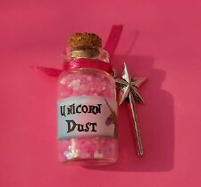 bottle of unicorn dust (pink) with a star wand charm and an organza bag