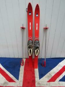 VINTAGE CHILDS RACING RED SKIS AND POLES WITH ANTIQUE SKI BOOTS ATTACHED 93Ccm