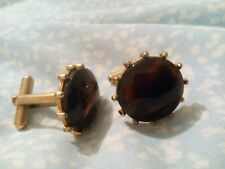 A Pair Of Brown Glass cufflinks With Tiger's Eye Stone Effect To Them.