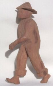 A primitively carved man with a hat, bare feet, and rolled up pants legs.