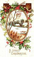 A Joyous Christmastide Holly City scene Gold Foil Embossed Vintage Postcard