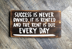 Success is never owned it is rented and the rent is due everyday wood sign