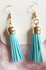 womans gold earring with pale blue tassel drop