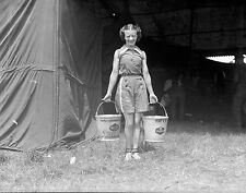 1930s Leslie Jones negative. Circus performer carries water buckets for elephant
