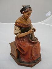 Grödner Holzschnitzerei: ältere, strickende Dame in Tracht, auf Holzbank sitzend