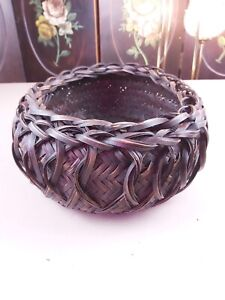 Dark brown near black woven oval basket, with detailed swirling figure eight