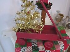Old toy red wagon with handle and wood wheels.  Display for Christmas.