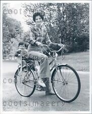 Pretty Woman Riding Bicycle With Child in Toddler Seat Press Photo