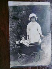 YOUNG GIRL WITH DOLL IN PRAM POSTCARD
