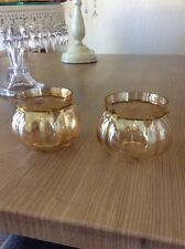 A PAIR OF GOLD GLASS TEA LIGHT HOLDES WITH GOLD JEWELS AROUND THE TOP